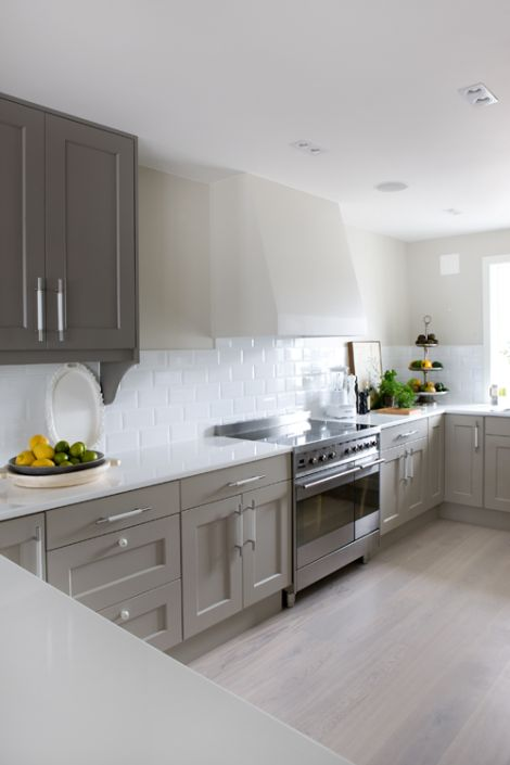 We think this grey kitchen featuring white tiling a white countertop